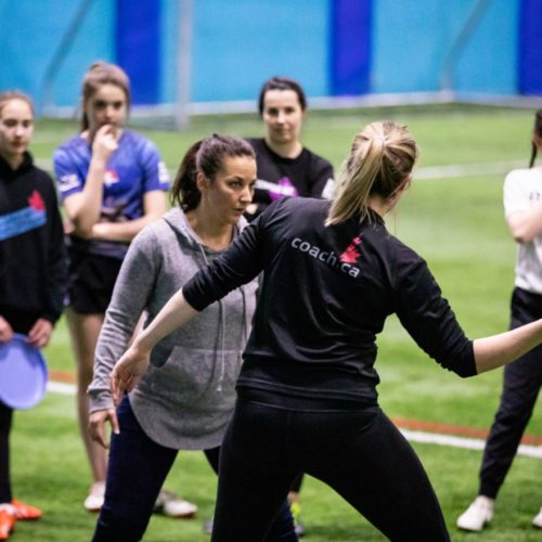Two female ultimate coaches demonstrate defensive positioning and breaking a mark while surrounded by youth players.